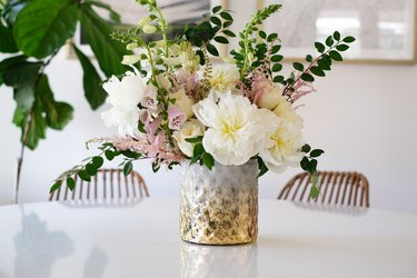 Textured vase with white and pink flowers with green leaves