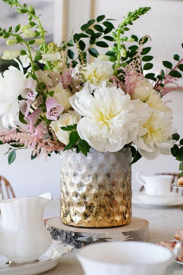Gold-white textured vase with white and pink flowers with foliage on dining table