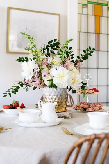 Dining table with flowers, china dishware in dining room with stained glass window