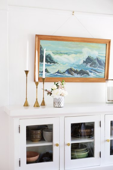 White dishware cabinet with gold candlesticks, vase of flowers, and seascape painting
