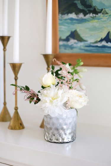 Vase of white and pink flowers on white counter with gold candlesticks and painting