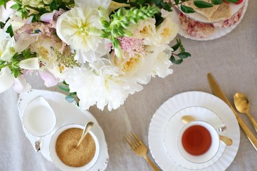 White and pink flowers with white china and gold utensils