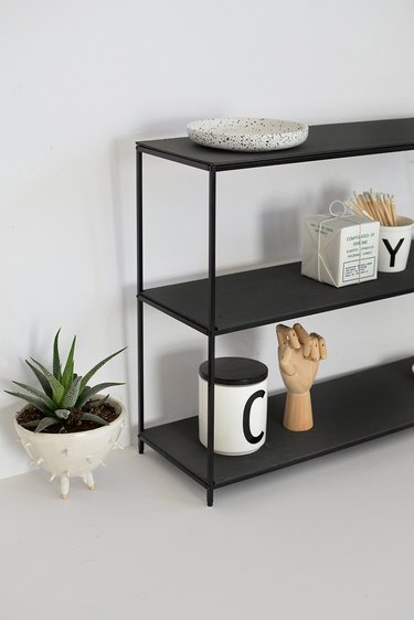 Black metal shelf with mugs and drafting tools in a white room next to small potted succulent in white plant holder