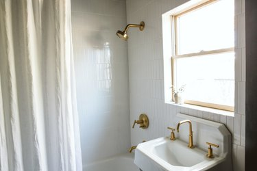 industrial farmhouse white sink with a gold faucet and white tiles in a bathroom