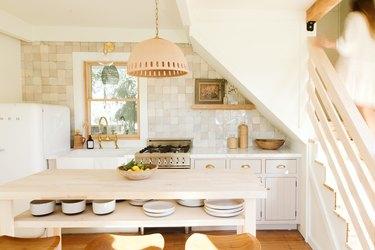 white Smeg refrigerator, pendant lamp and wooden kitchen island with beige tiled backsplash