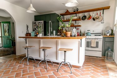 Kitchen with terra-cotta floor, industrial stools, wood counter kitchen island, bell pendant lights gray cabinets, and wood shelves