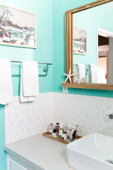 Makeup Organizer Ideas in Bathroom with blue walls, white tile, mirror, towel rack, tray with lotions, make up, painting, white sink.
