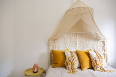 Yellow Room Ideas in Yellow and off white pillows, white bedding, canopy, white vintage bed frame, white walls.