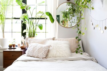 Boho bedroom with blush and off-white textured bedding, several plants, and round wall mirror