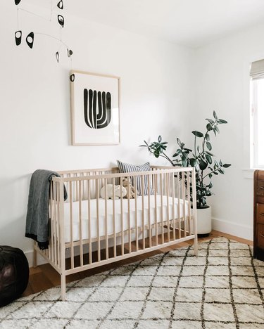 Gender-neutral nursery with white and beige organic color palette and black abstract mobile and artwork