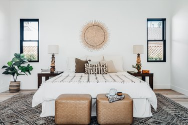 Minimal boho bedroom with black and white color palette and lots of texture, including sunburst rattan wall hanging over bed