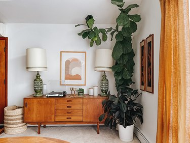 Corner of boho living room featuring very tall fiddle leaf fig, mid-century sideboard, and matching tall green table lamps
