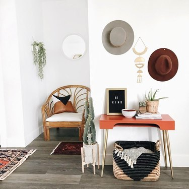 White-dominant southwestern-inspired entryway with rattan armchair and orange midcentury console