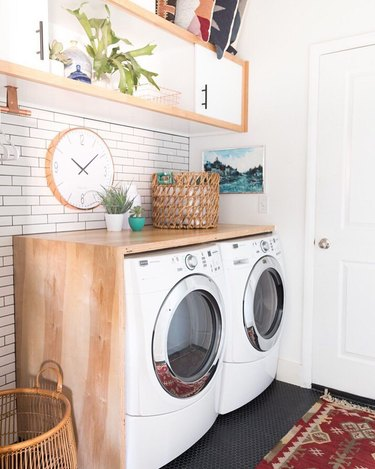 Laundry room with white subway tile, red kilim rug, and horizontal cubed wall shelf