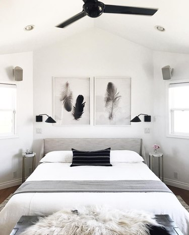 Minimal black and white symmetrical bedroom with pair of feather prints above bed