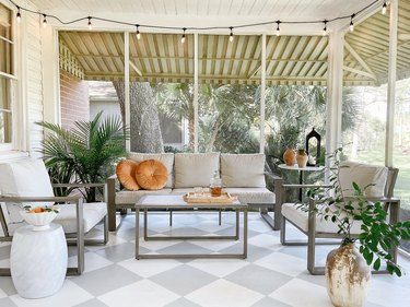 Sunroom with gray furniture—a three-seat sofa and two armchairs—and gray and white checkerboard floor