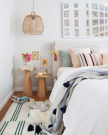White bedroom with pastel throw pillows and woven bell-shaped pendant light