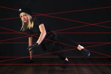 Cat burglar negotiating laser beam alarm system