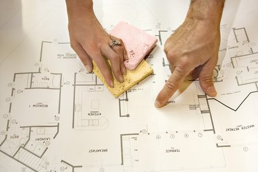 Hands with blueprints and paint samples