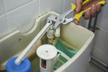 Close up of hand repairing toilet