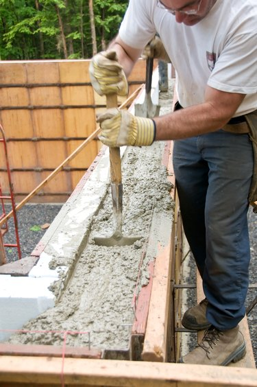 Construction worker stirring concrete inside mold