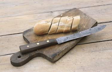 Slices of bread by knife on cutting board