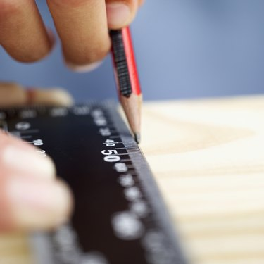 close-up of a person's hands marking a wooden plank with a ruler and a pencil