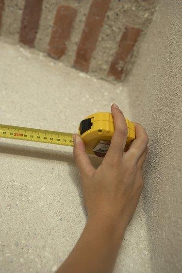 Hand using tape measure
