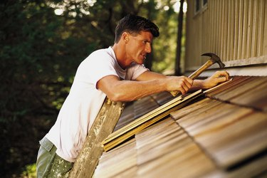 Man installing roof shingles