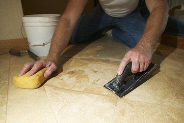Close-up of a marble mason's hands as he scrapes and wipes the floor he is working on