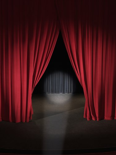 Empty stage with curtains slightly open and spotlight on