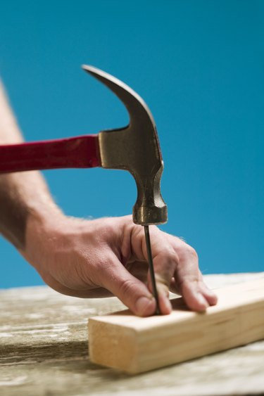 Person hammering nail into wood