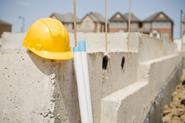 Construction Hat, New Home Foundation and Blueprints