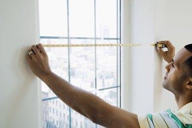 Man measuring window size