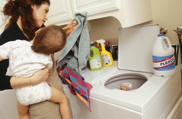 Mother and child (21-24 months) doing laundry