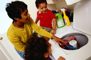 Mother Teaching Her Children How To Do Laundry