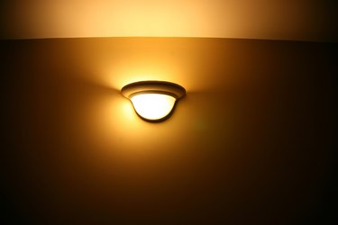 Glowing light fixture on wall