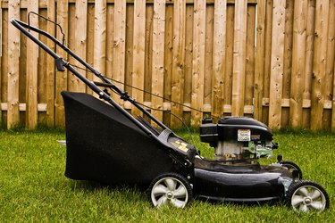 Power lawnmower in yard with fence