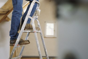Man standing on step ladders, legs only