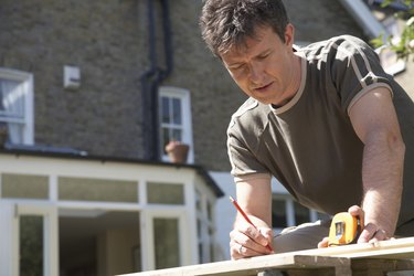 Man leaning on workbench in garden, using pencil and tape measure