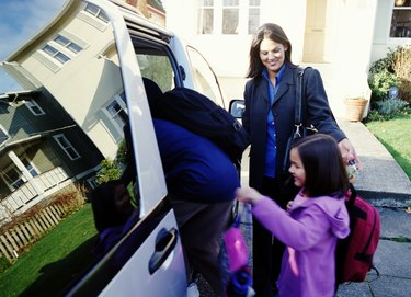 Mother helping son and daughter (6-8) get into mini van