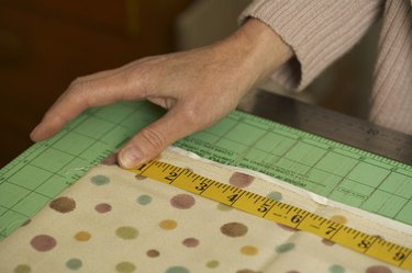 Close-up of hands of mature woman measuring textile