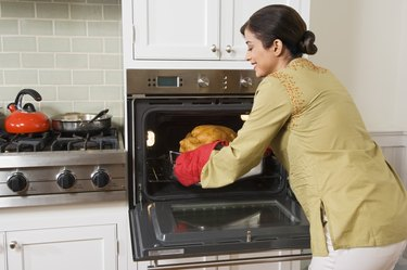 Woman taking Thanksgiving turkey out of oven