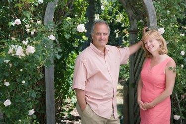 Couple posing outdoors under arbor