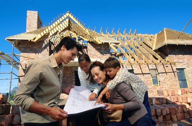 Family with blueprints at construction site