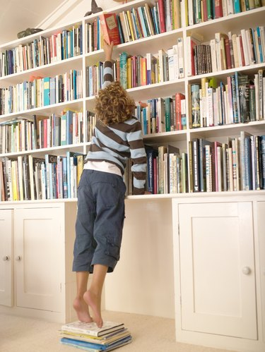 """""""Boy (7-9) standing on books, reaching for top book shelf, rear view"""""""