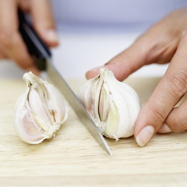 Woman's hands chopping garlic with a knife on a wooden board