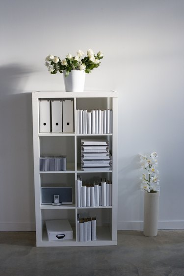 Bookcase and bouquets in sparse home office