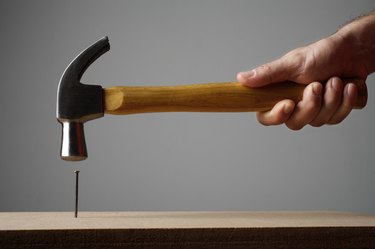 Hand using hammer on nail
