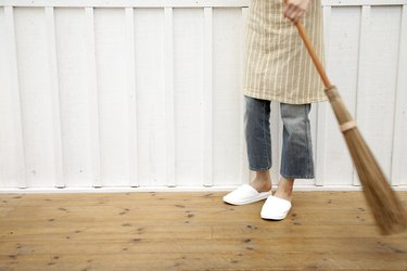 Woman sweeping floor using Japanese style broom in home